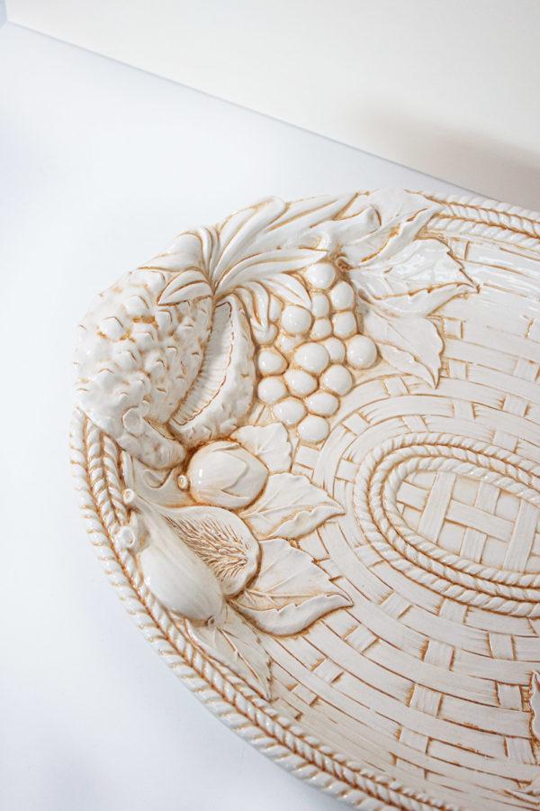 Piatto di forma ovale con due manici alle estremità. Stile country, con decorazioni rupestri in ceramica fatte a mano da artigiani italiani. Ideale come centrotavola, piatto da portata, fruttiera e soprammobile.