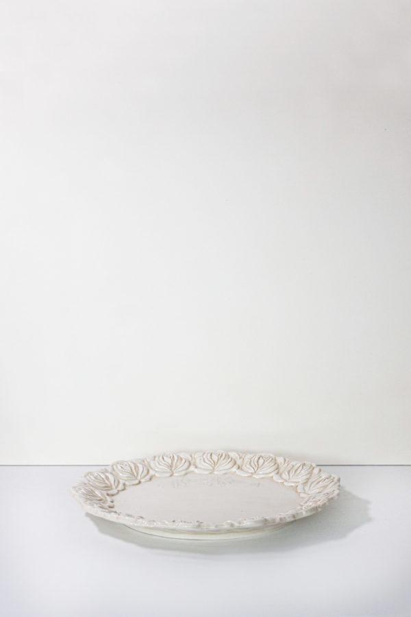 Piatto in ceramica bianca fatto a mano in Italia, di forma circolare con cornice di rose in rilievo.