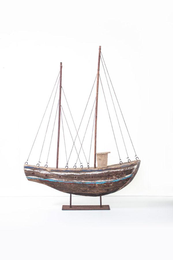 Battello realizzato in legno, con particolari in ferro e corda. Il piedistalo è realizzato in legno e ferro arrugginito.